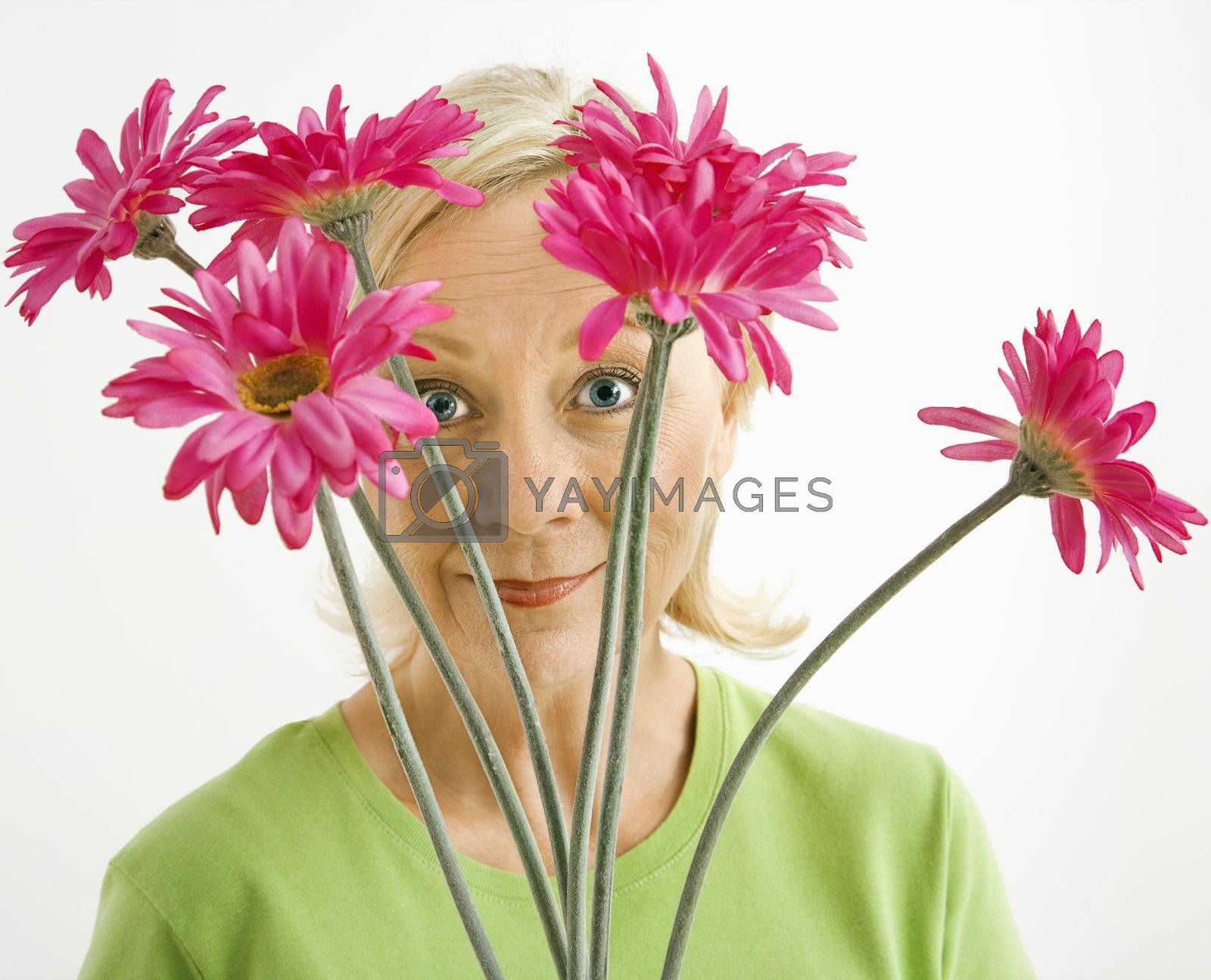 Portrait of smiling adult blonde woman looking through bouquet of pink flowers at viewer.