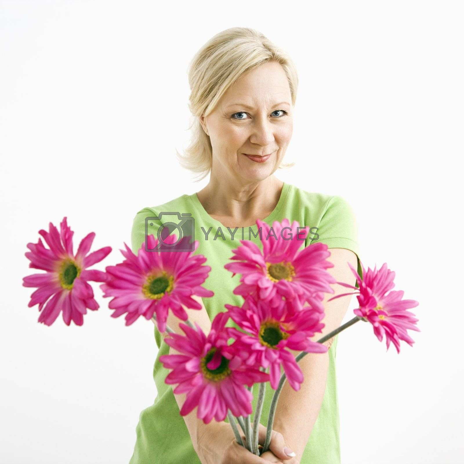 Portrait of smiling adult blonde woman giving bouquet of pink flowers to viewer.