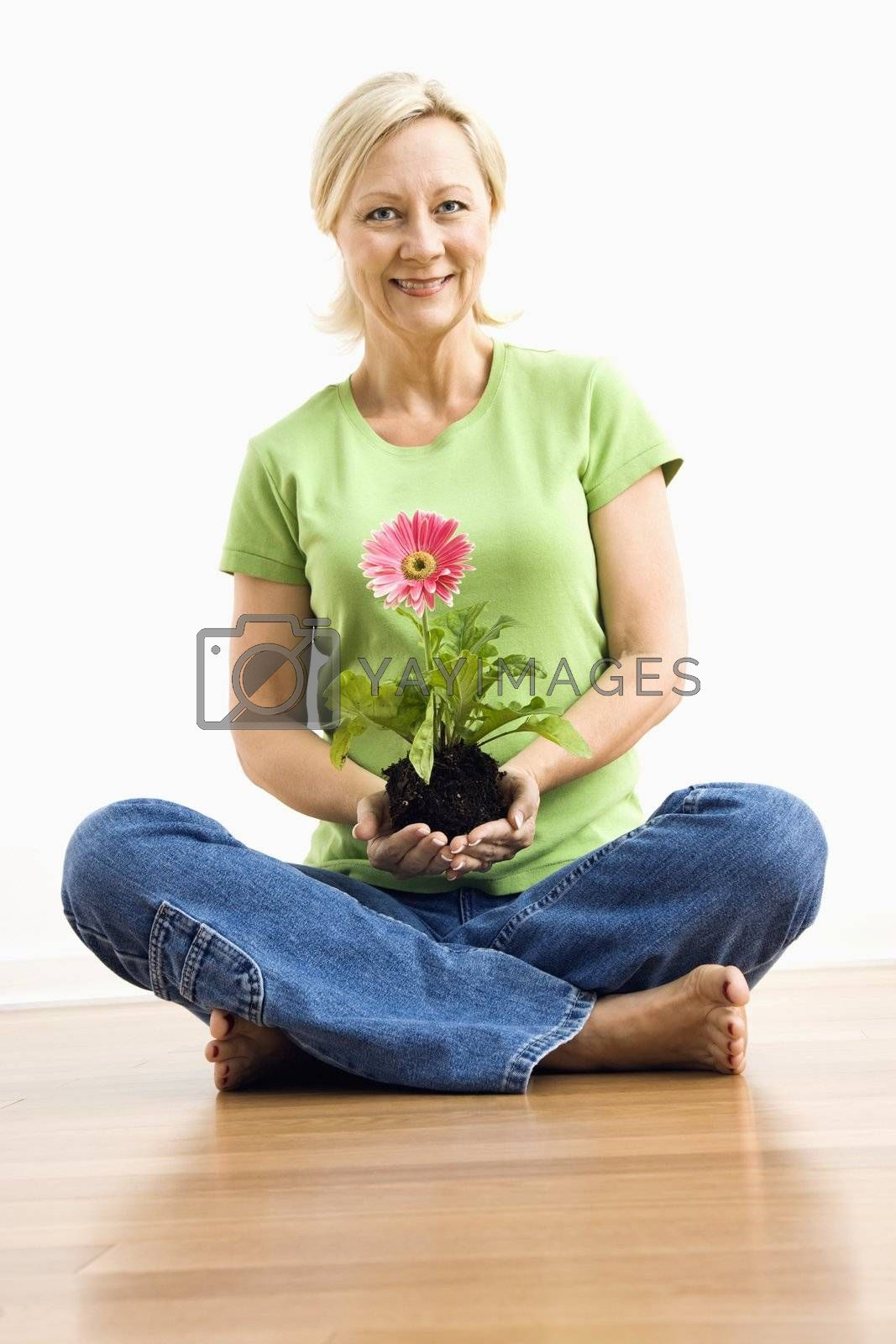 Portrait of smiling adult blonde woman sitting on floor holding pink gerber daisy plant.