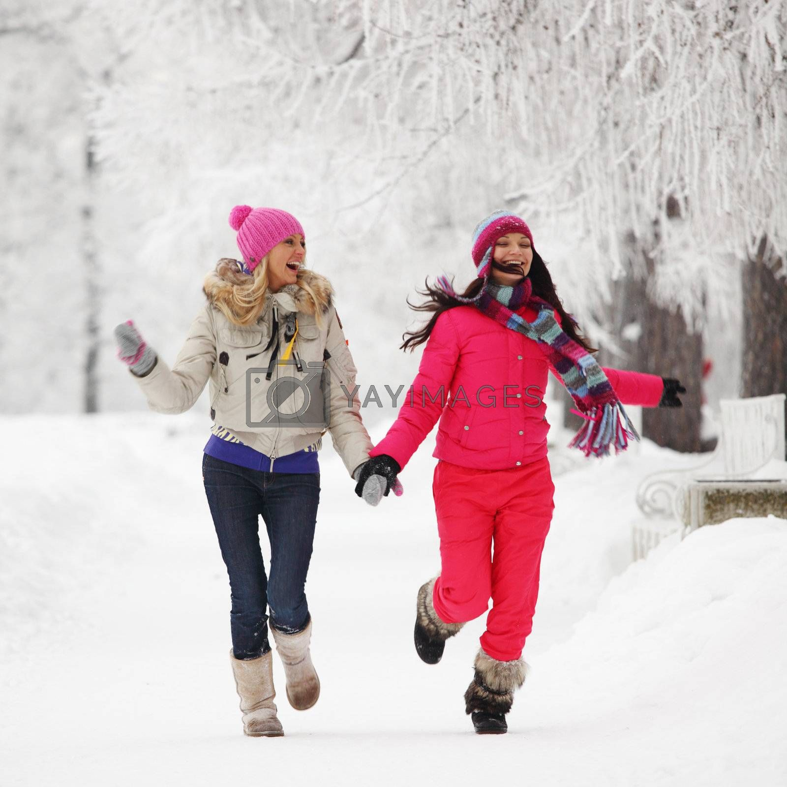 two winter women run by snow frosted alley