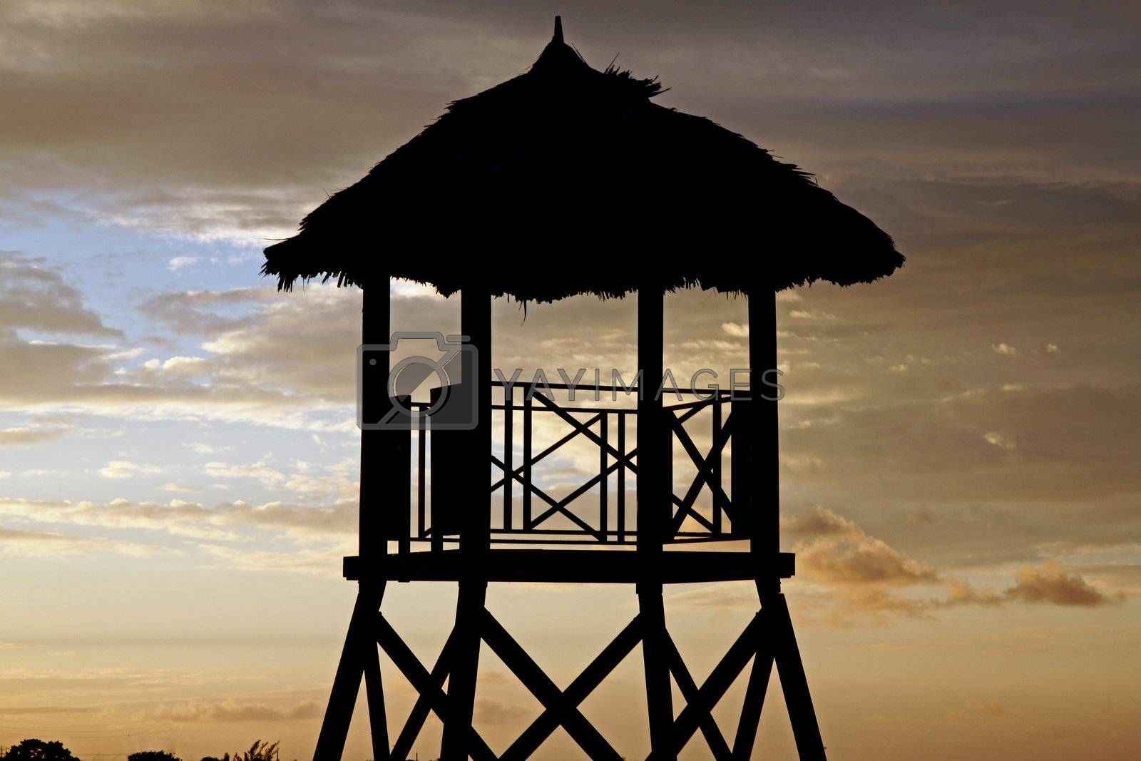 Tropical watchtower overlooking a beach silhouette at sunset