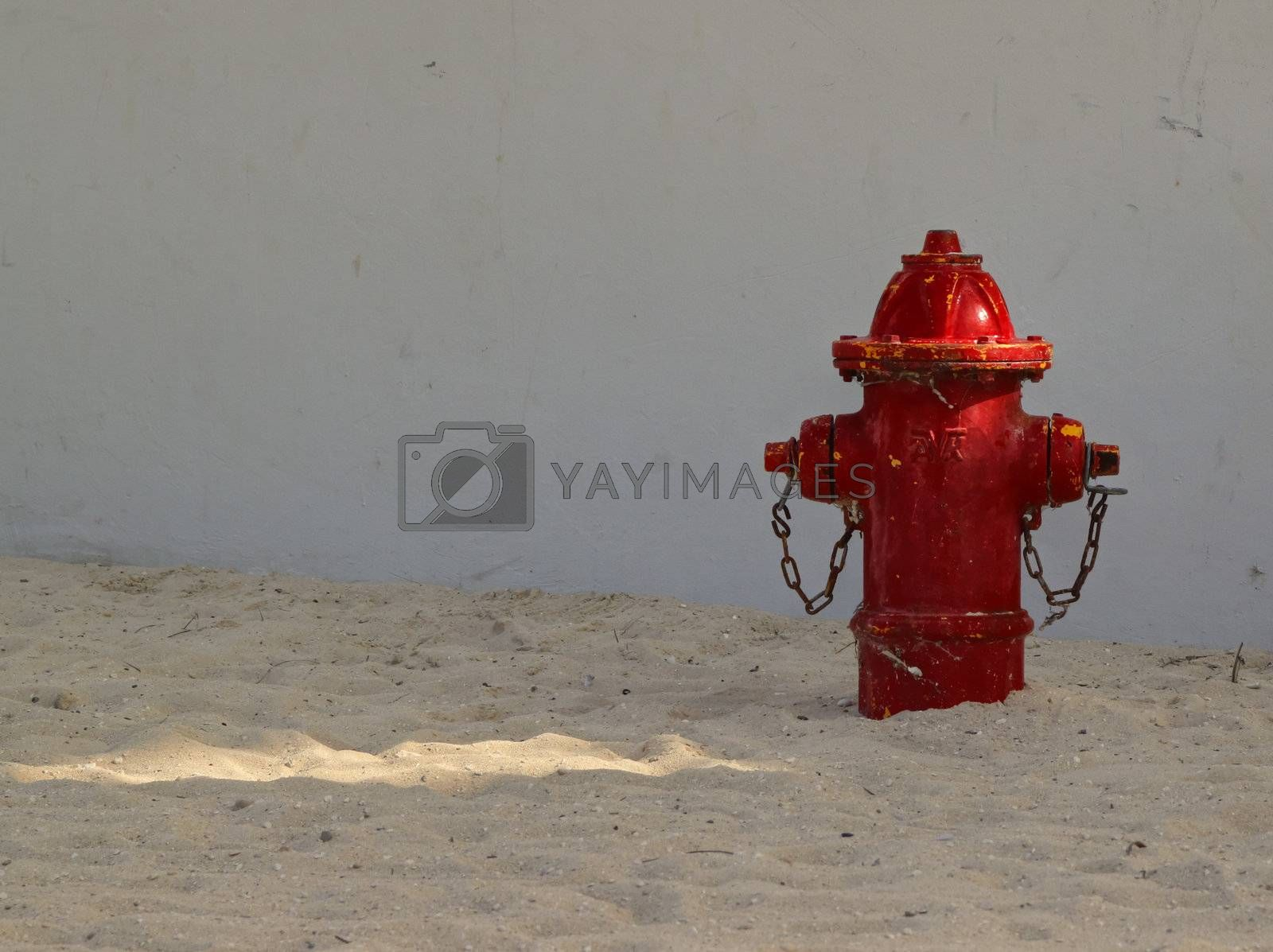 Right side view of red fire hydrant on a sandy beach