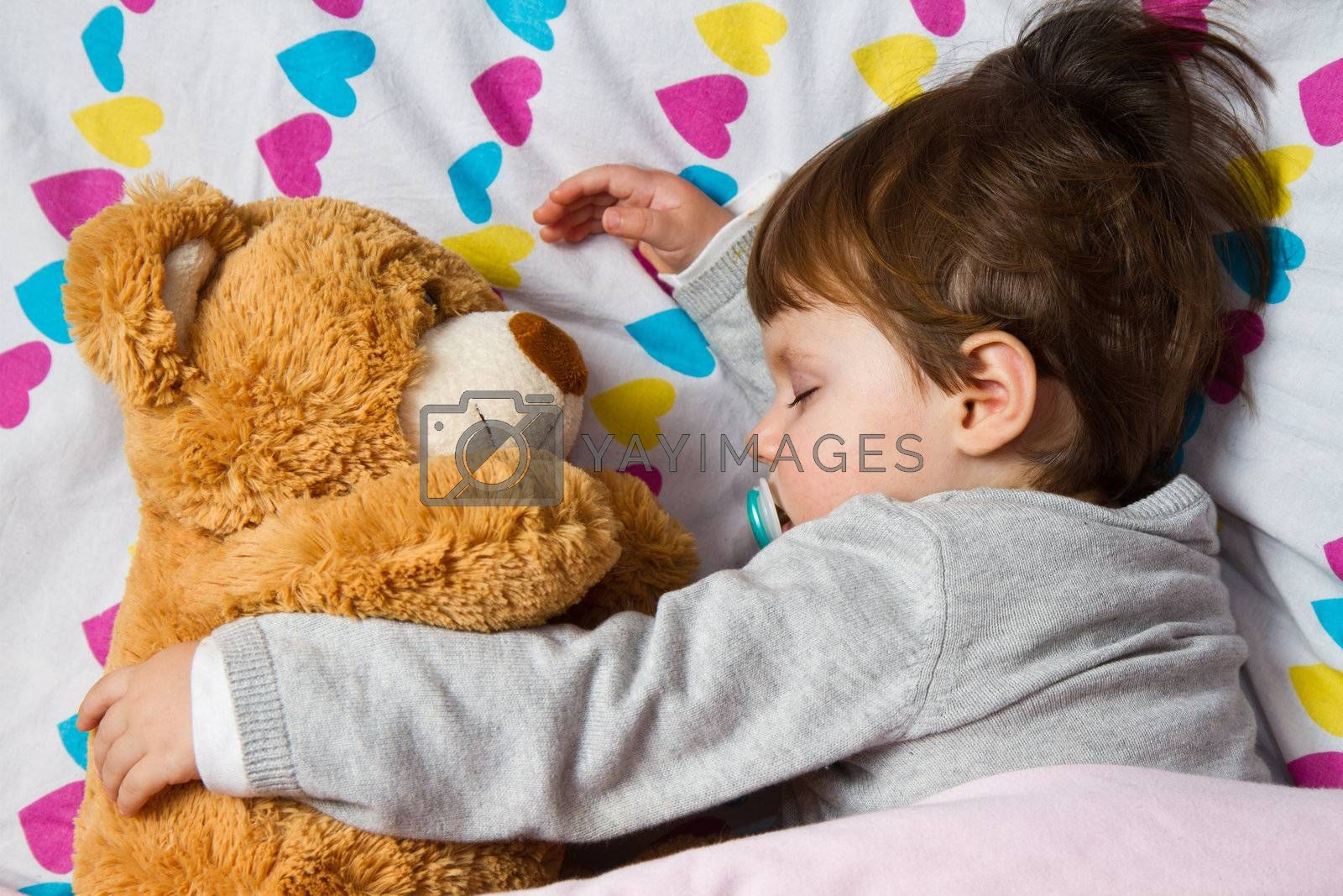 Royalty free image of Sweet child sleeping with teddy bear  by lsantilli