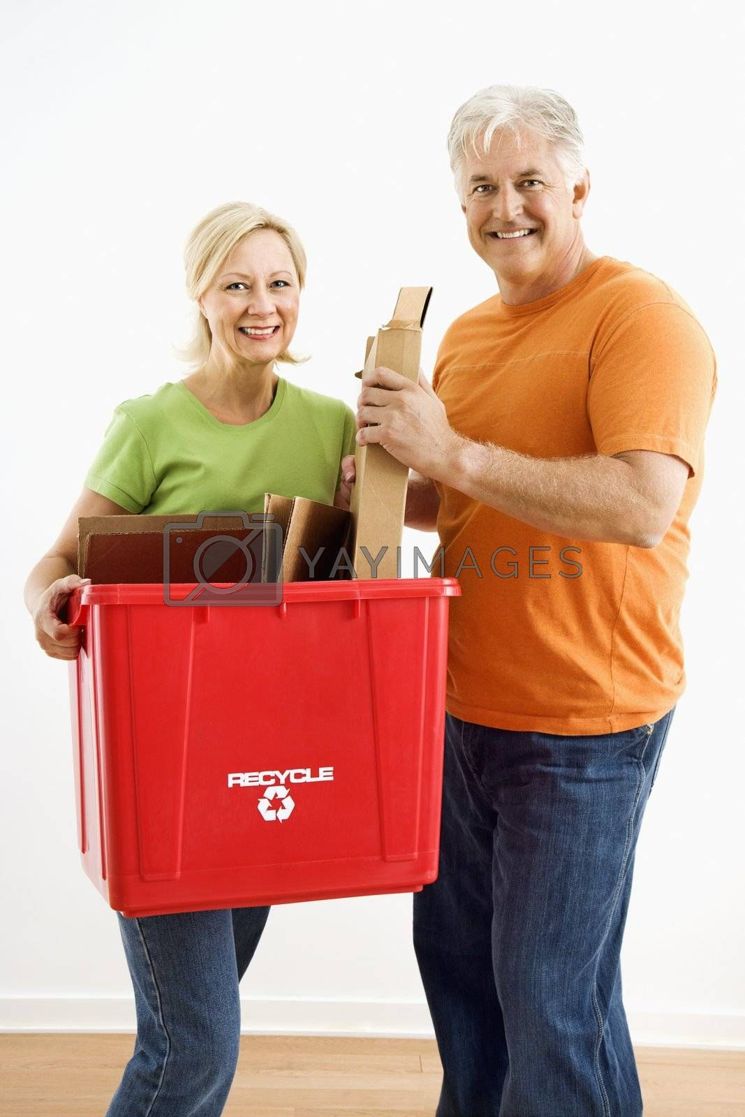Man and woman smiling while holding recycling bin.