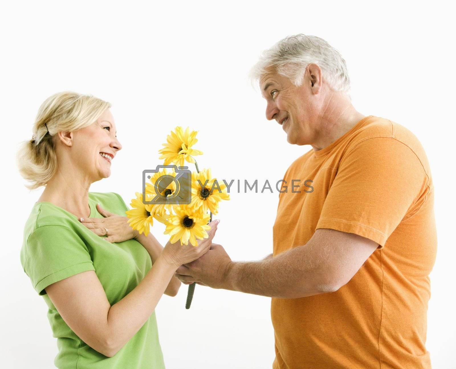 Middle-aged man giving woman bouquet of yellow flowers.
