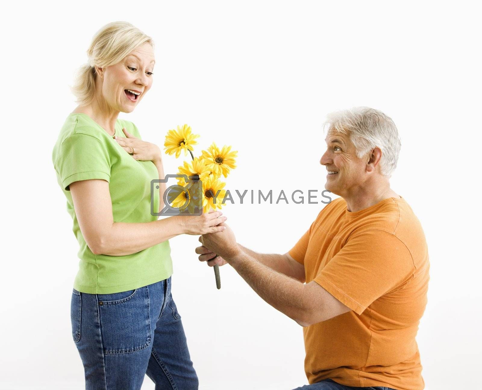 Middle-aged man on bended knee giving woman bouquet of yellow flowers.