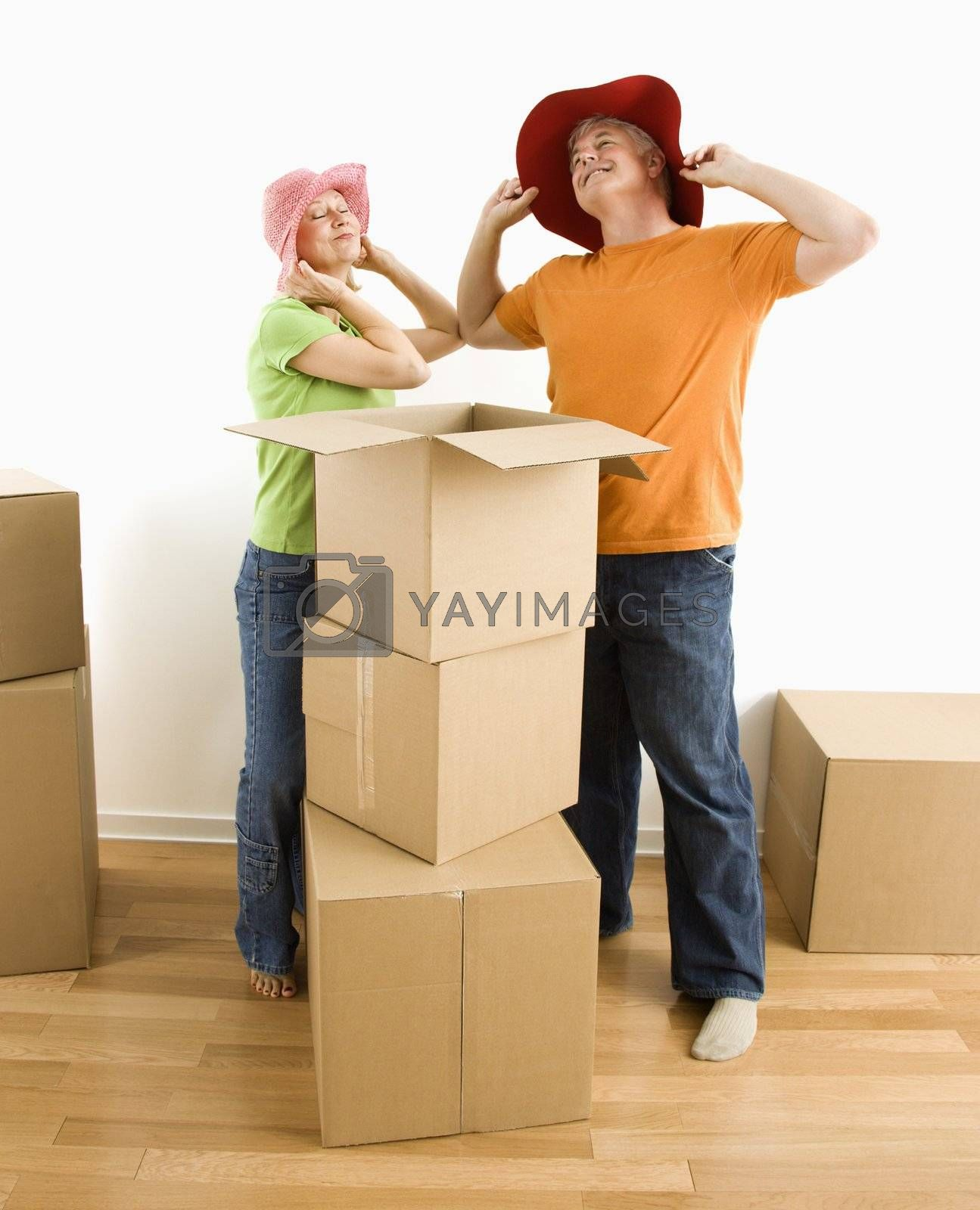 Middle-aged couple trying on silly hats while packing or unpacking moving boxes.