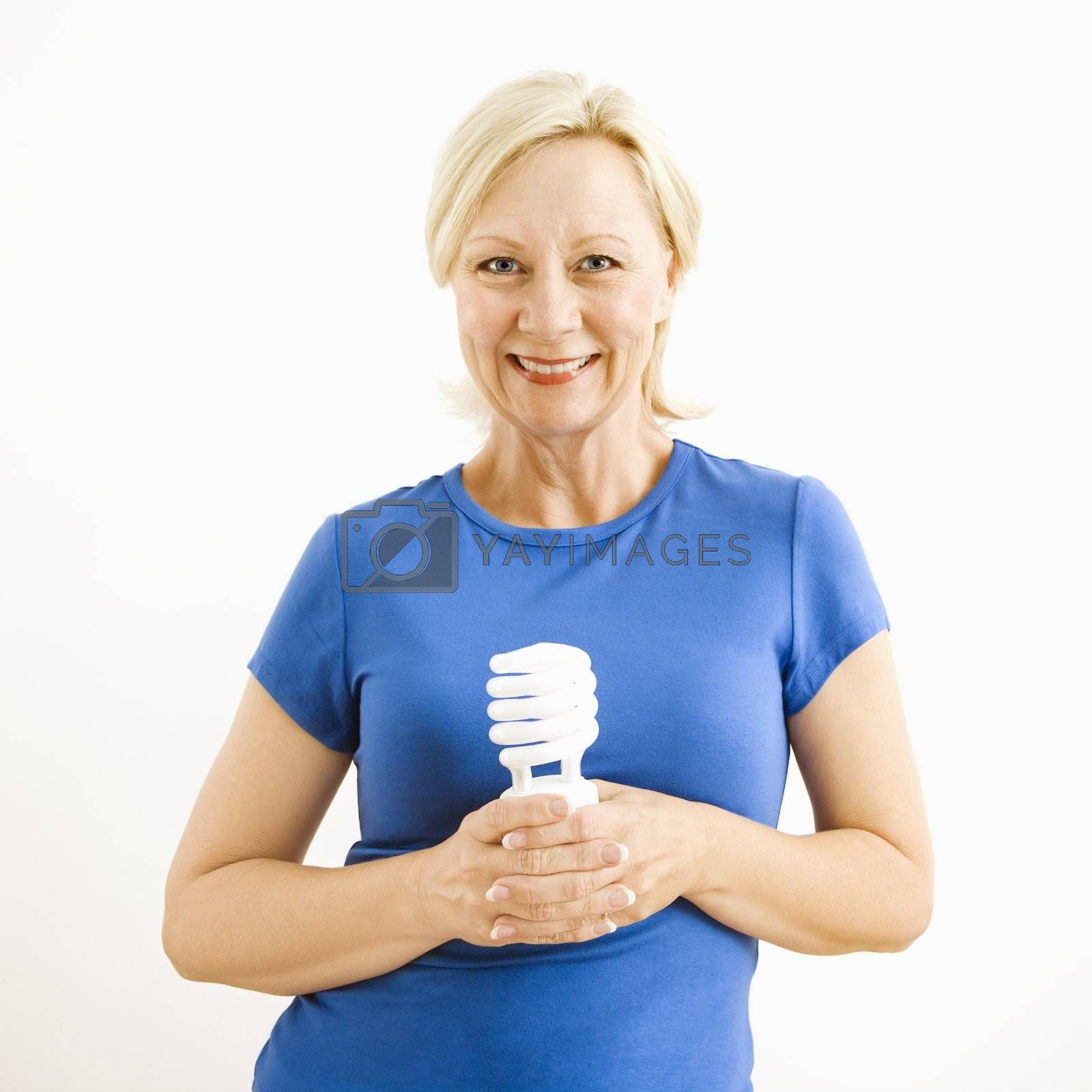 Portrait of smiling adult blonde woman holding energy-saving lightbulb.