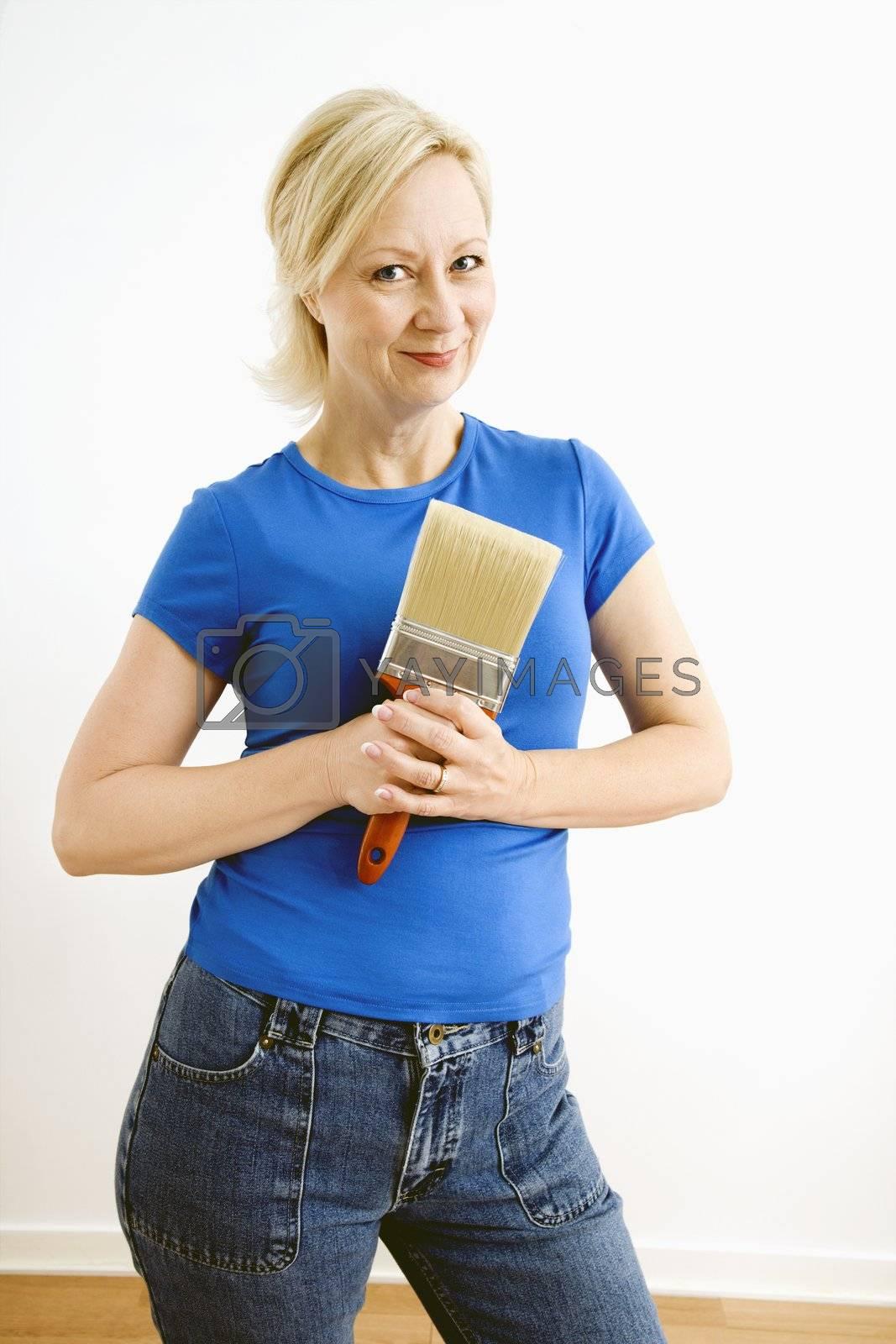 Portrait of smiling adult blonde woman holding paintbrush.