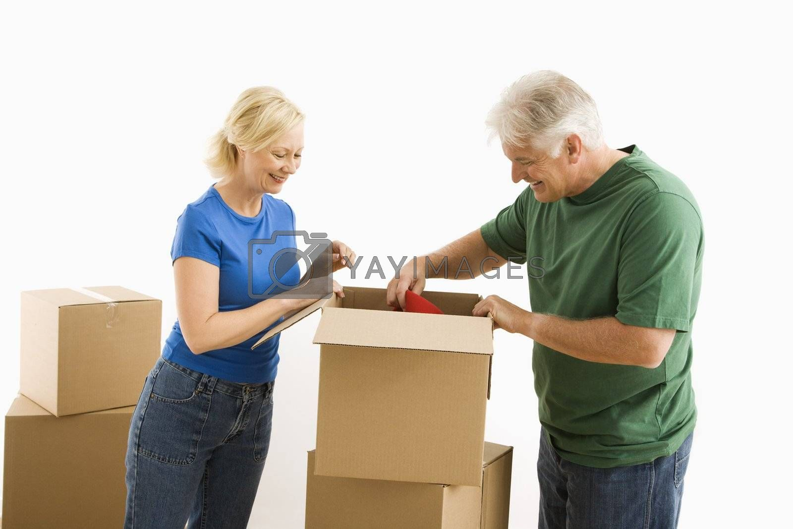 Middle-aged couple packing or unpacking moving boxes.