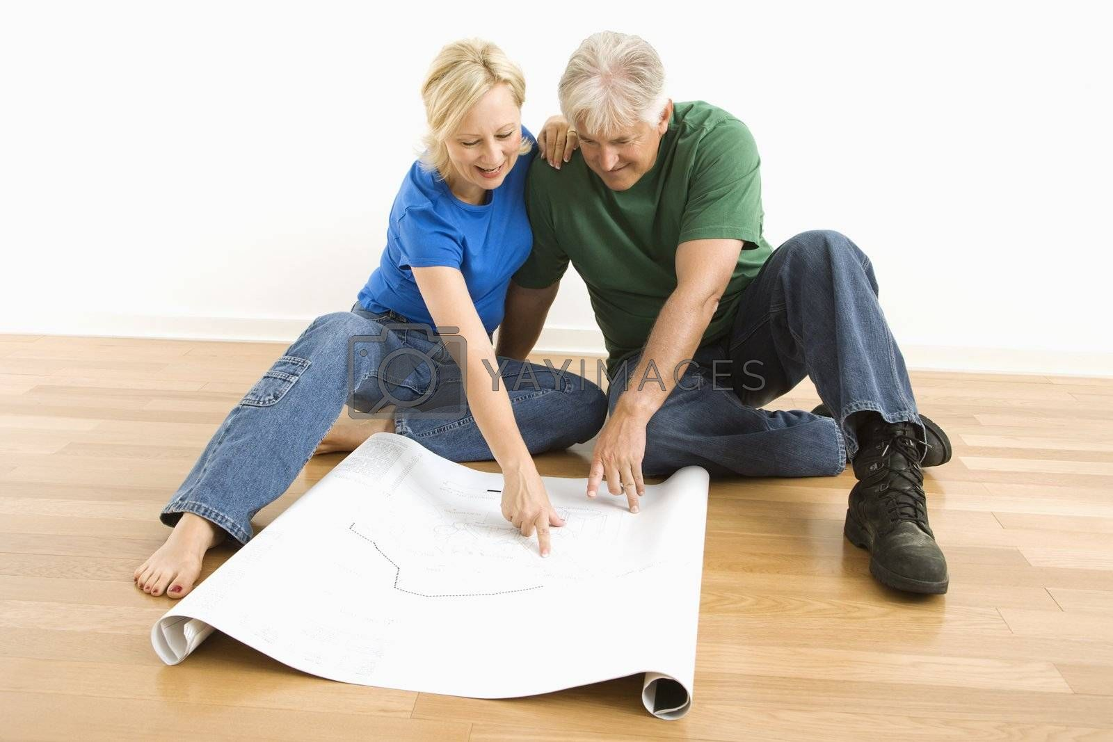Middle-aged couple sitting on floor looking at and discussing architectural blueprints together.