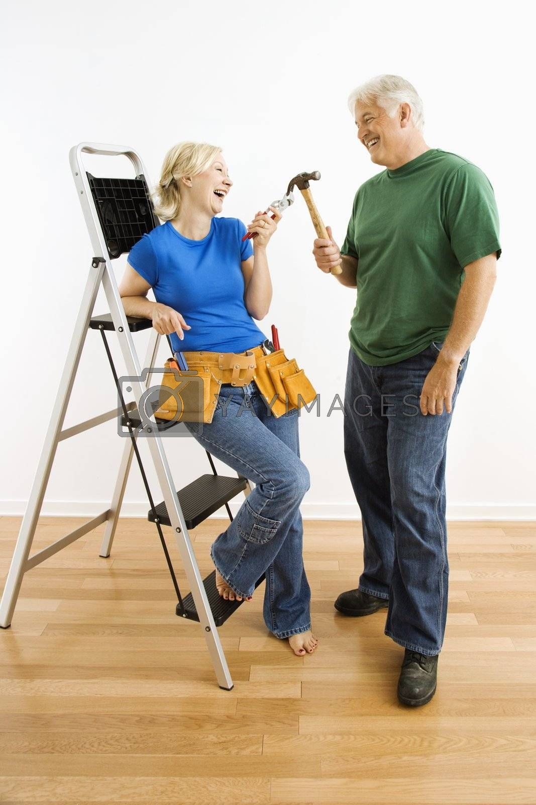 Middle-aged couple with household tools next to ladder.