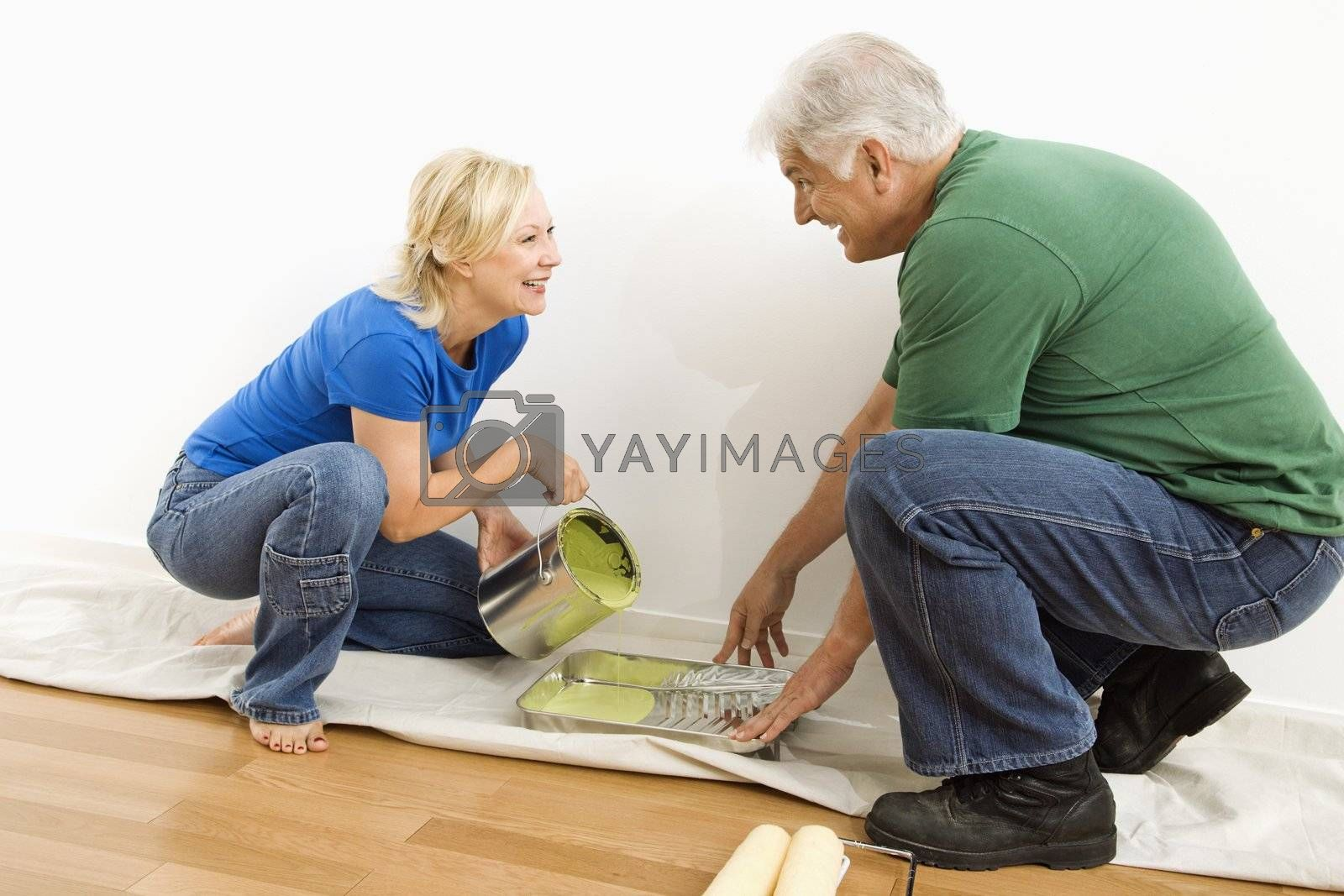 Middle-aged couple pouring paint into tray on drop cloth.