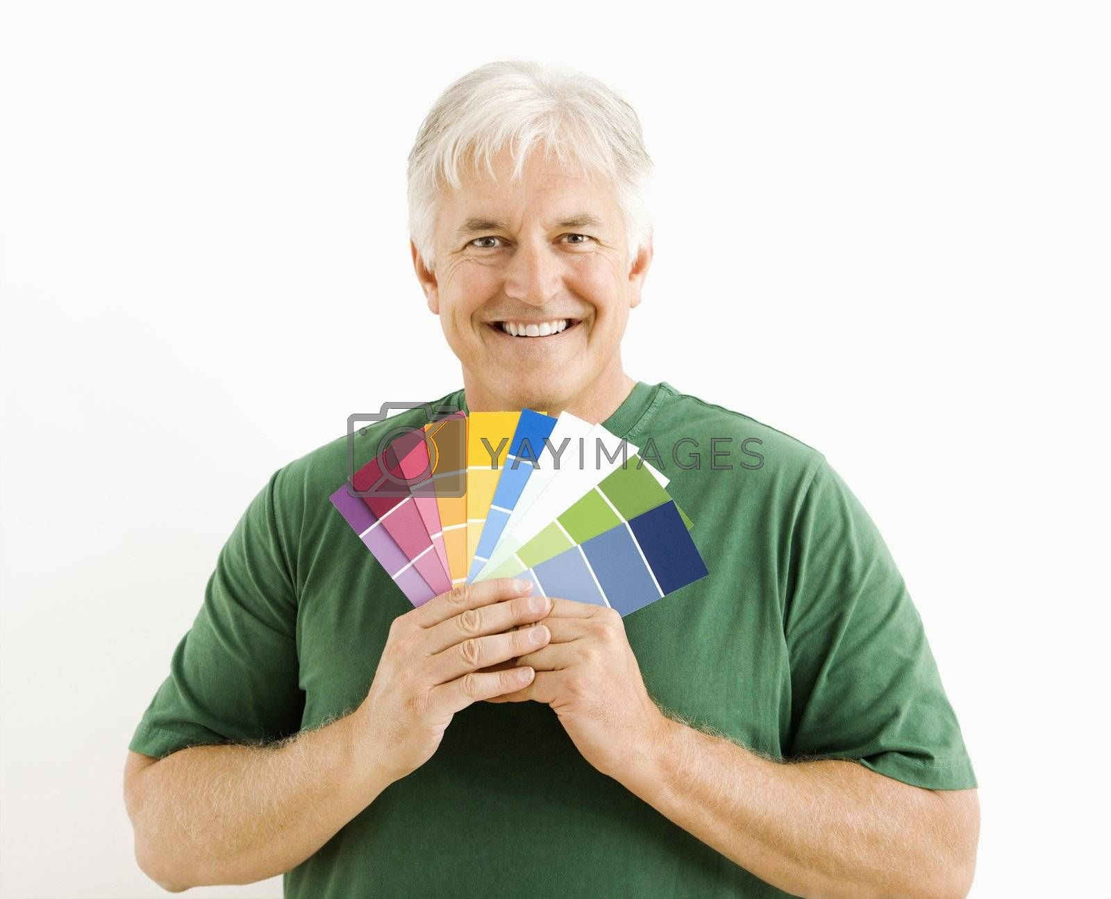 Middle-aged man holding up paint swatches.