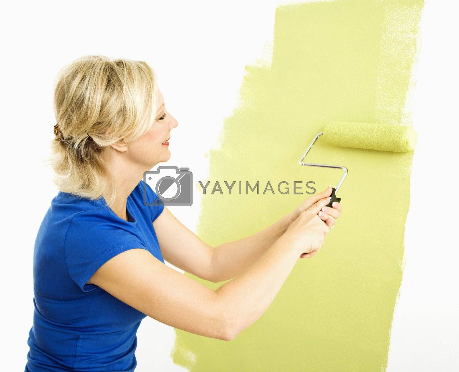 Middle-aged woman painting wall green with paint roller.