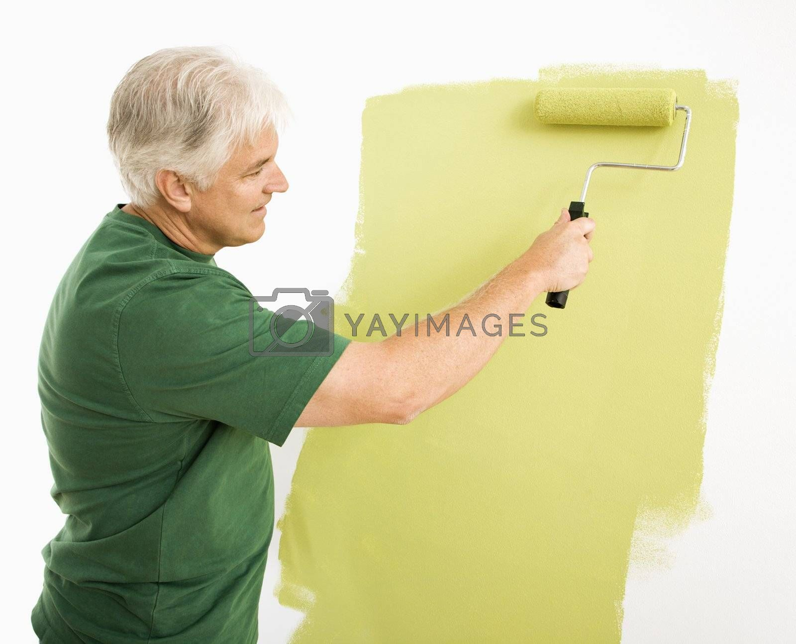Middle-aged man painting wall green with paint roller.