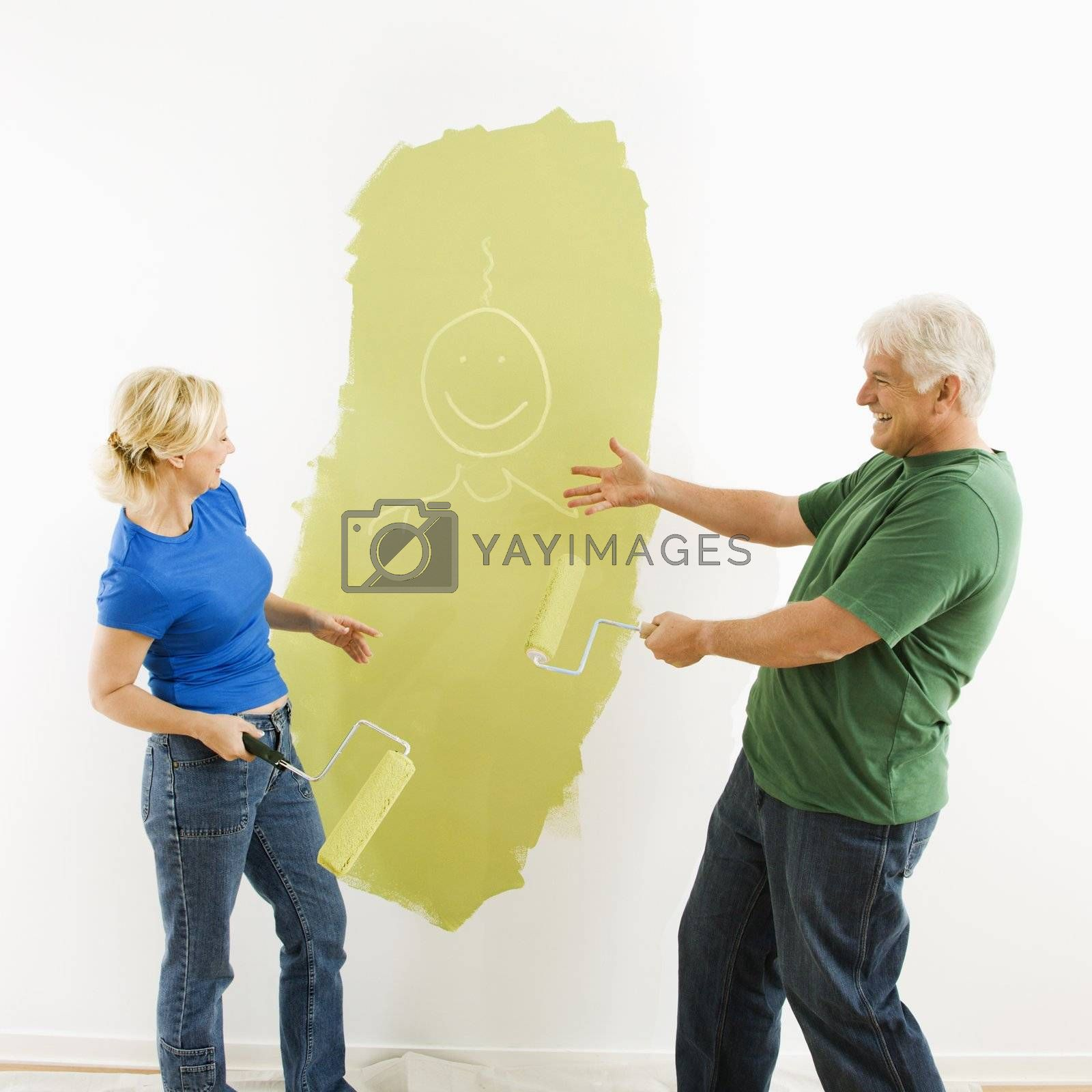 Middle-aged couple painting wall green finger-painting smiley face figurine for fun.