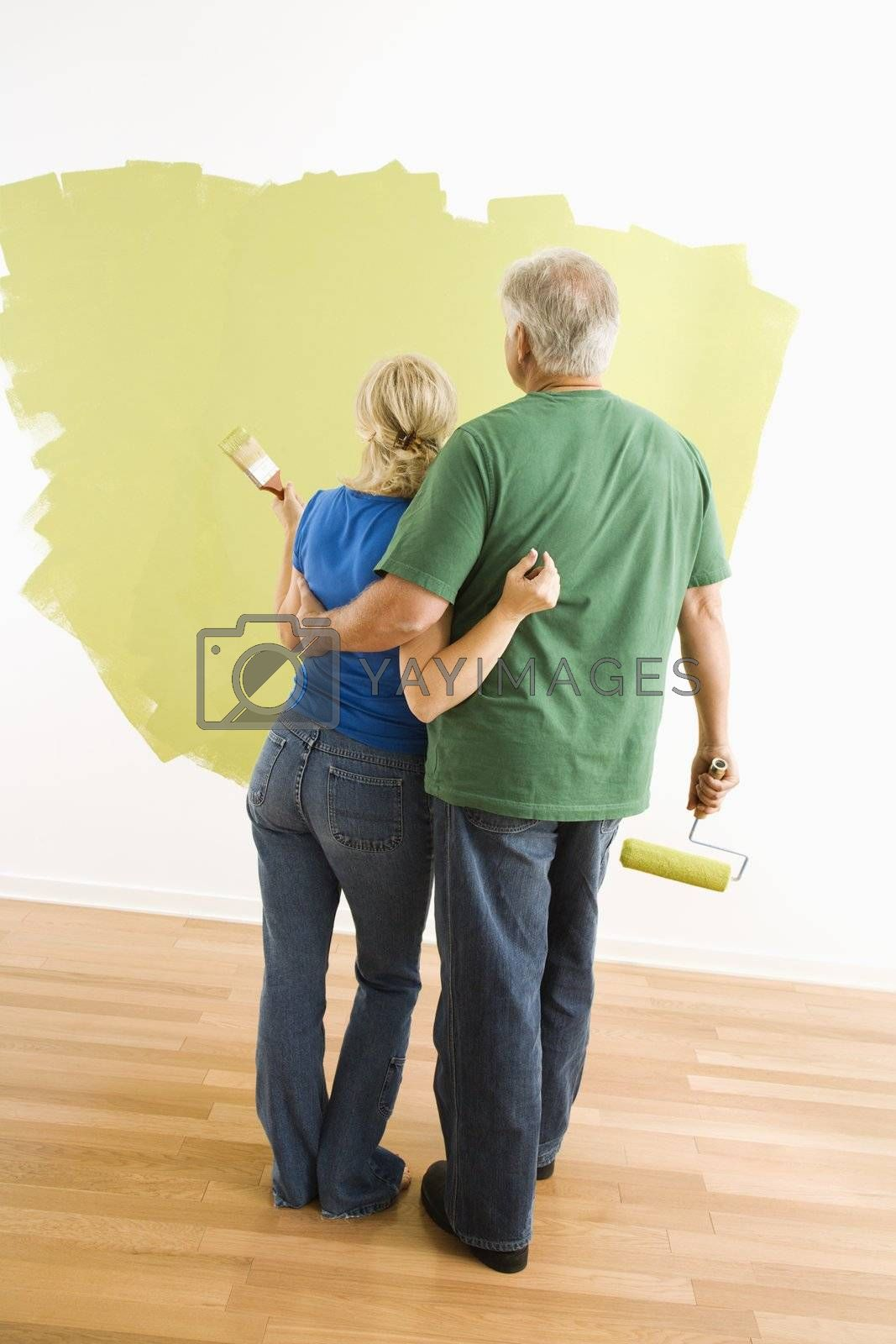 Middle-aged couple painting wall green observing their work.