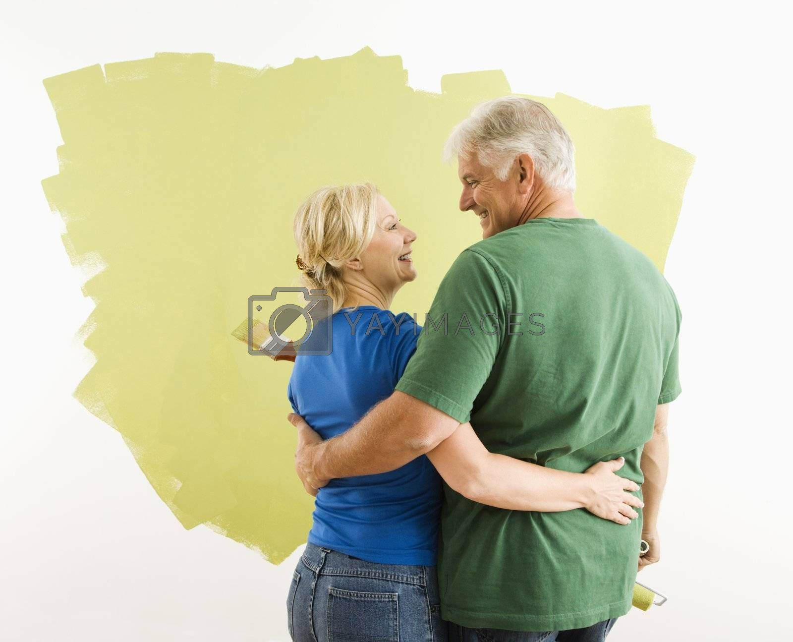 Middle-aged couple painting wall green observing and discussing their work.
