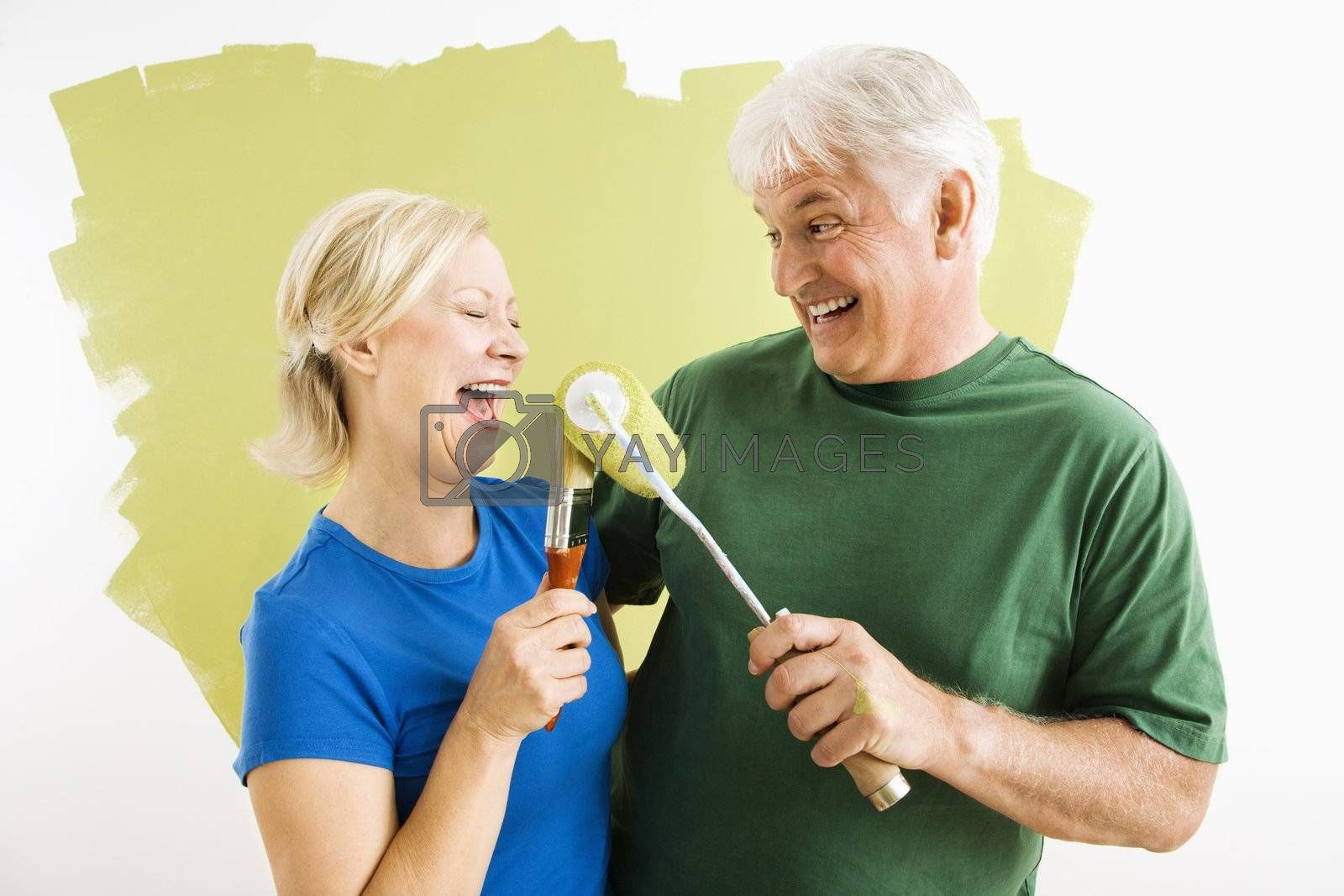 Middle-aged couple painting wall green playing with paint utensils.
