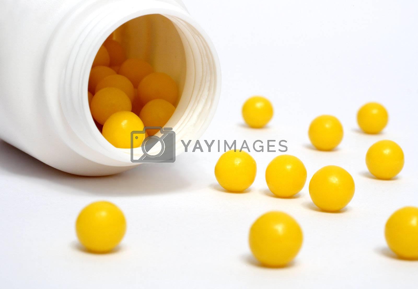 yellow vitamin dradees around white bottle