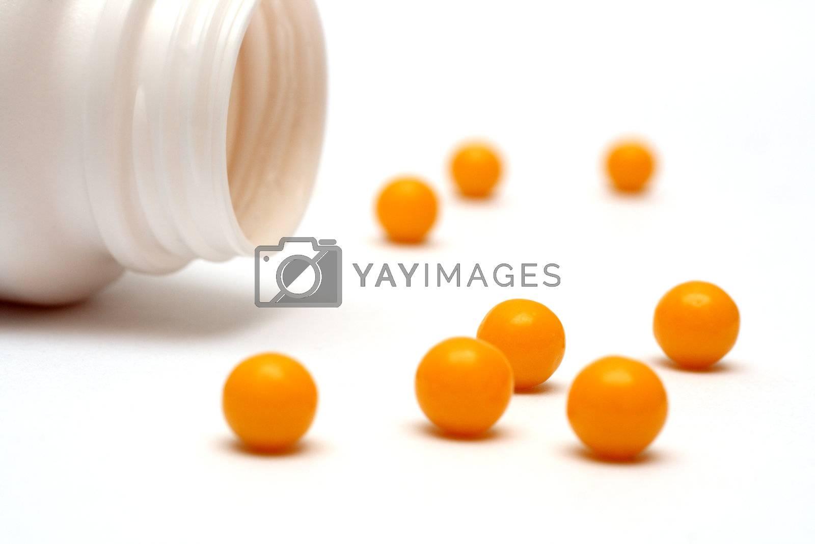 yellow vitamin dradees near white bottle