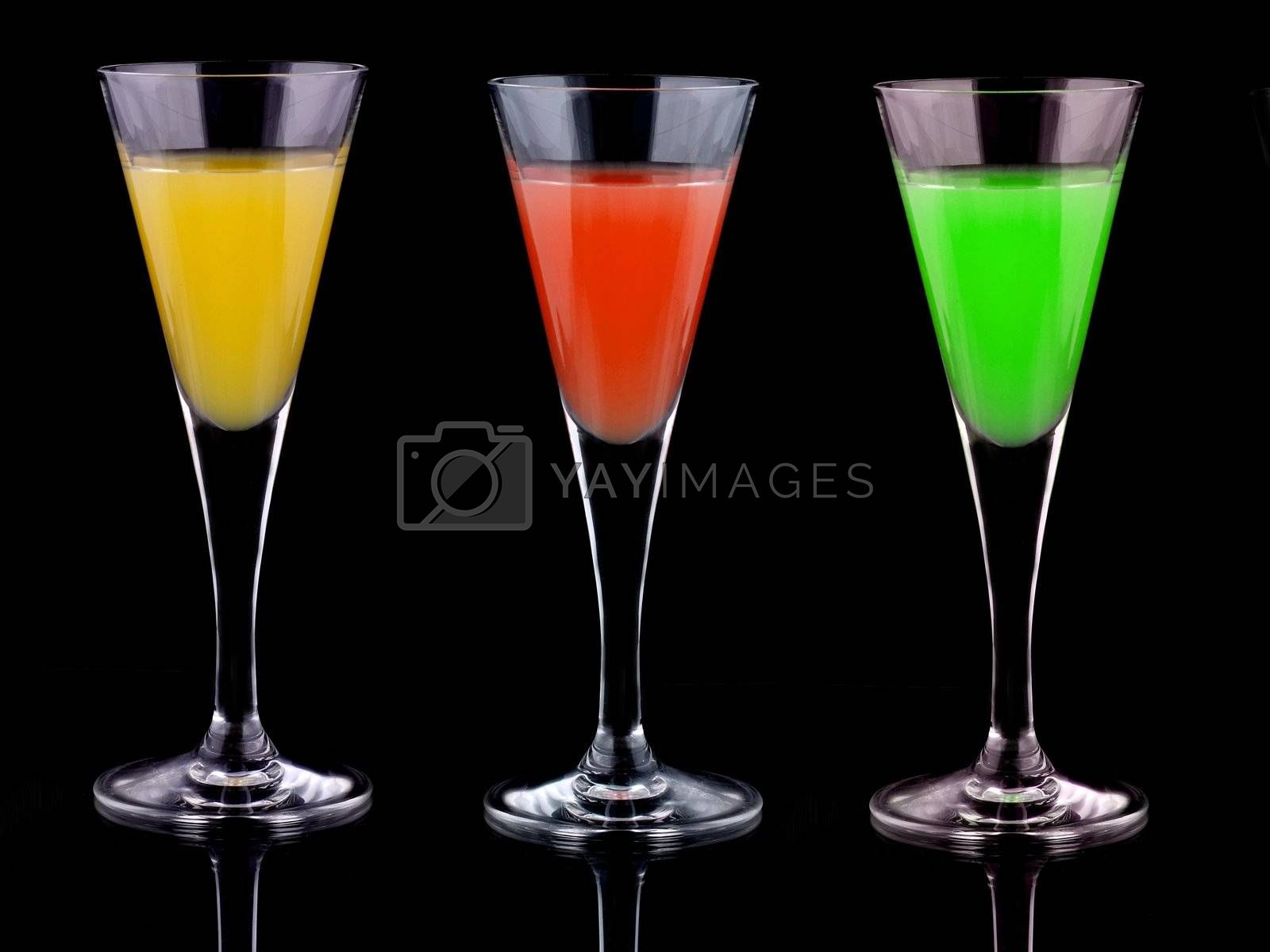 three glasses with liquor of diferent colors