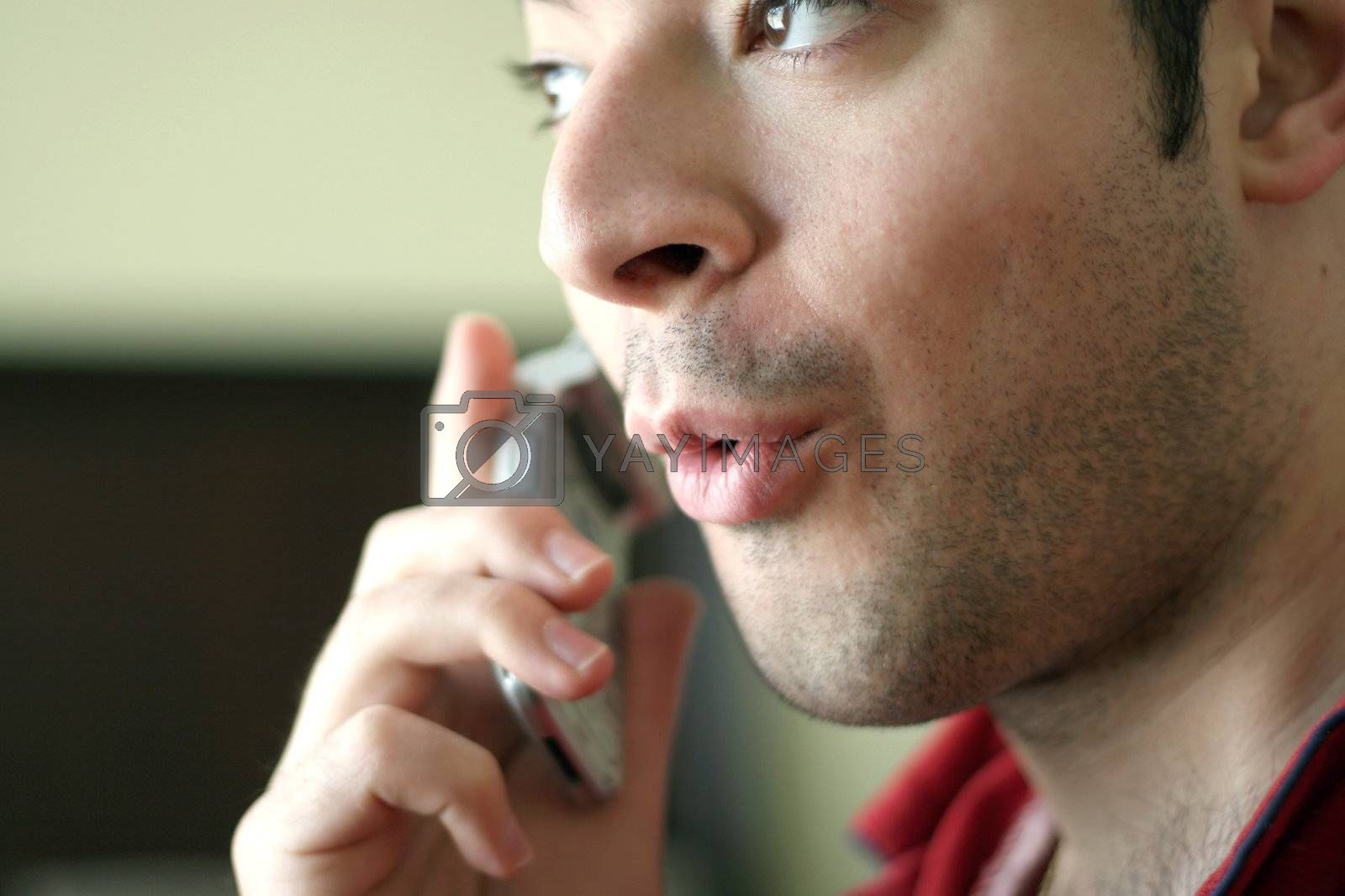 A man on his cell phone speaking excitedly or acting surprised about what he is hearing.