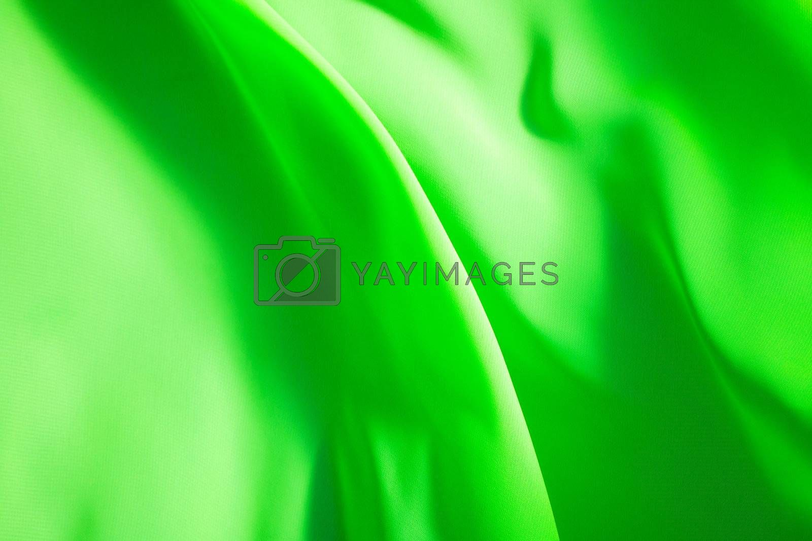 green fabric winds waves, creating a beautiful background of the folds