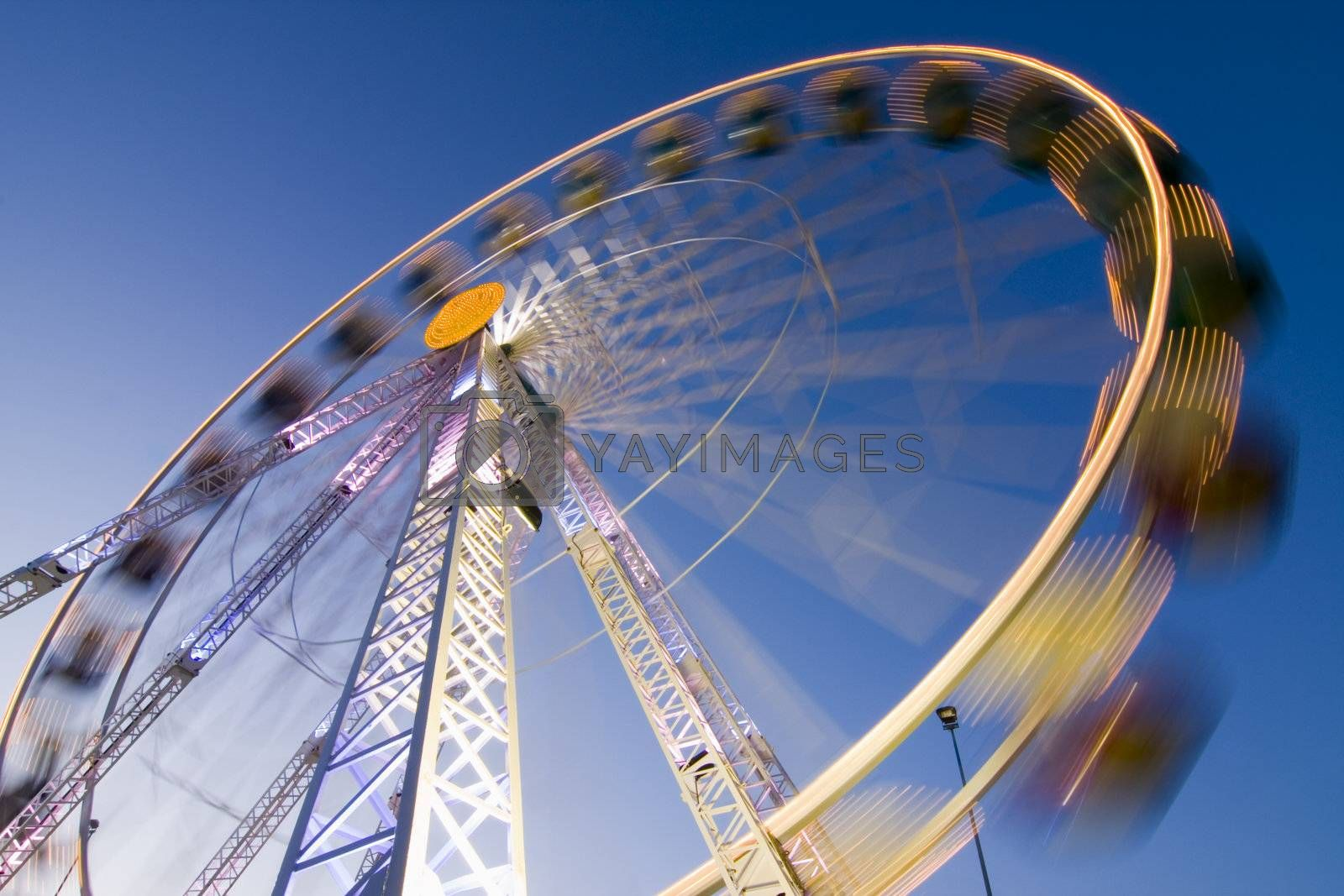 Big wheel on a fun fair with colorful lights. Motion blurred. Long exposure time with tripod.