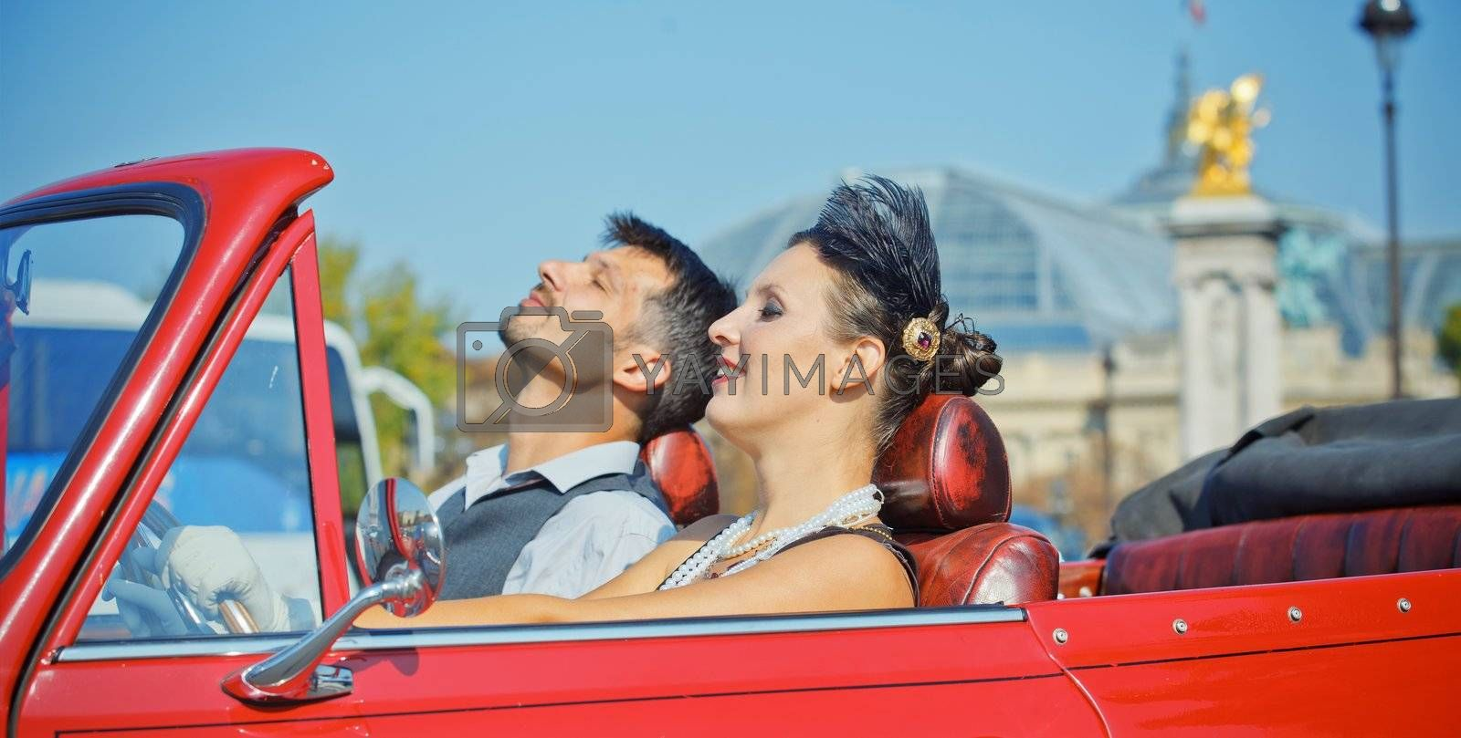 Romance in Paris. Young happy couple in retro-style travel in a car in Paris