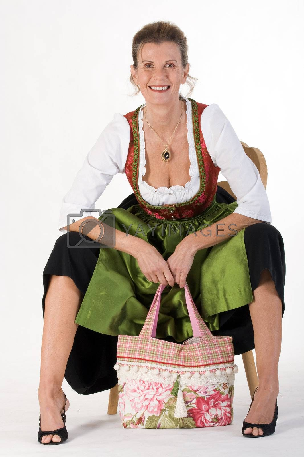 elderly woman in Bavarian costume dress with modern bag is sitting on a chair laughing