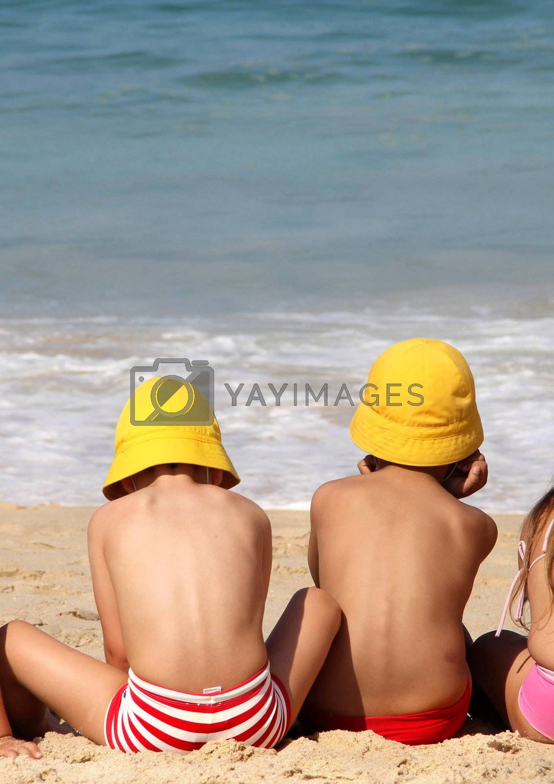 Funny cute brothers on the beach in the yellow vivid panamas