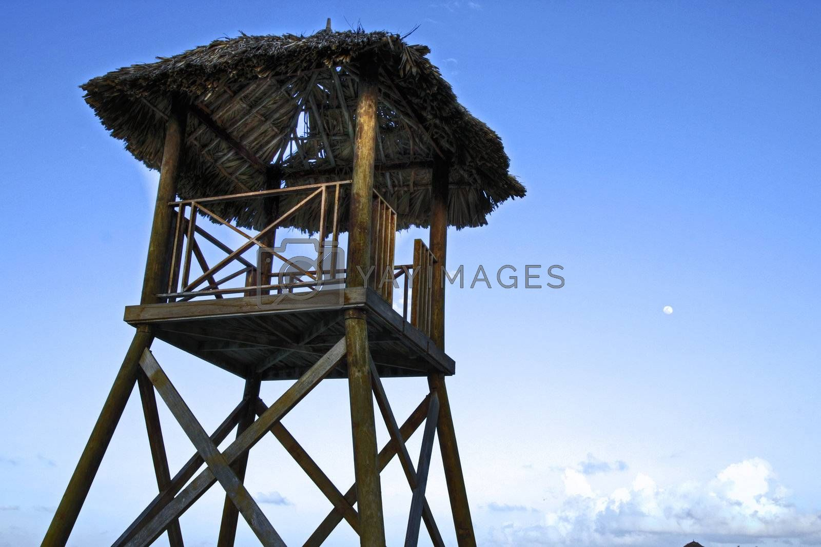 Tropical watchtower overlooking a beach in silhouette