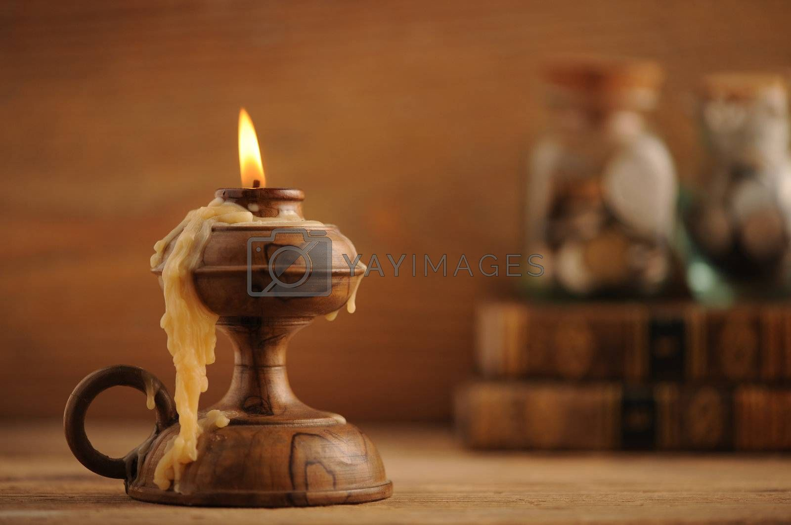 old candle on a wooden table, old books in the background