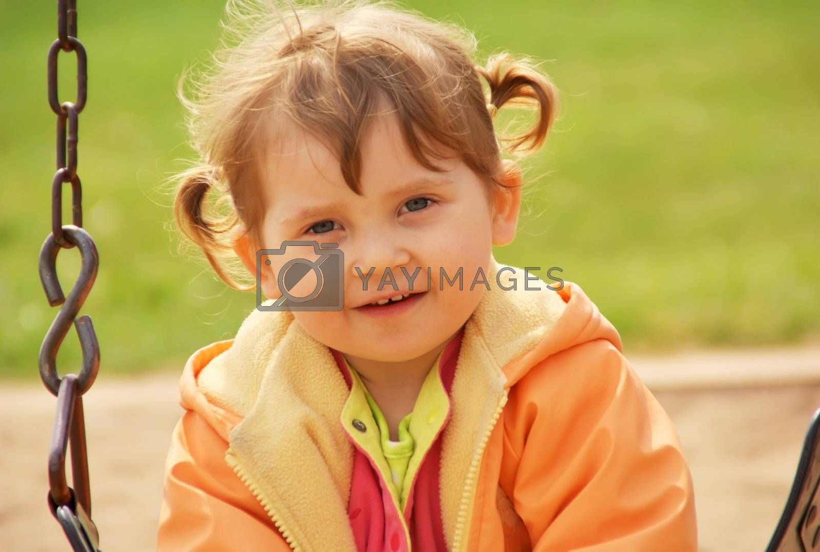 Little girl at park playground. Green grass  background. Spring time.
