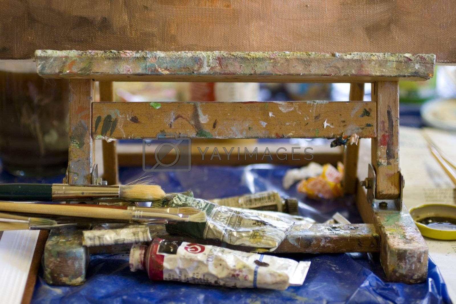 Atelier. Palette with colors, easel in the background