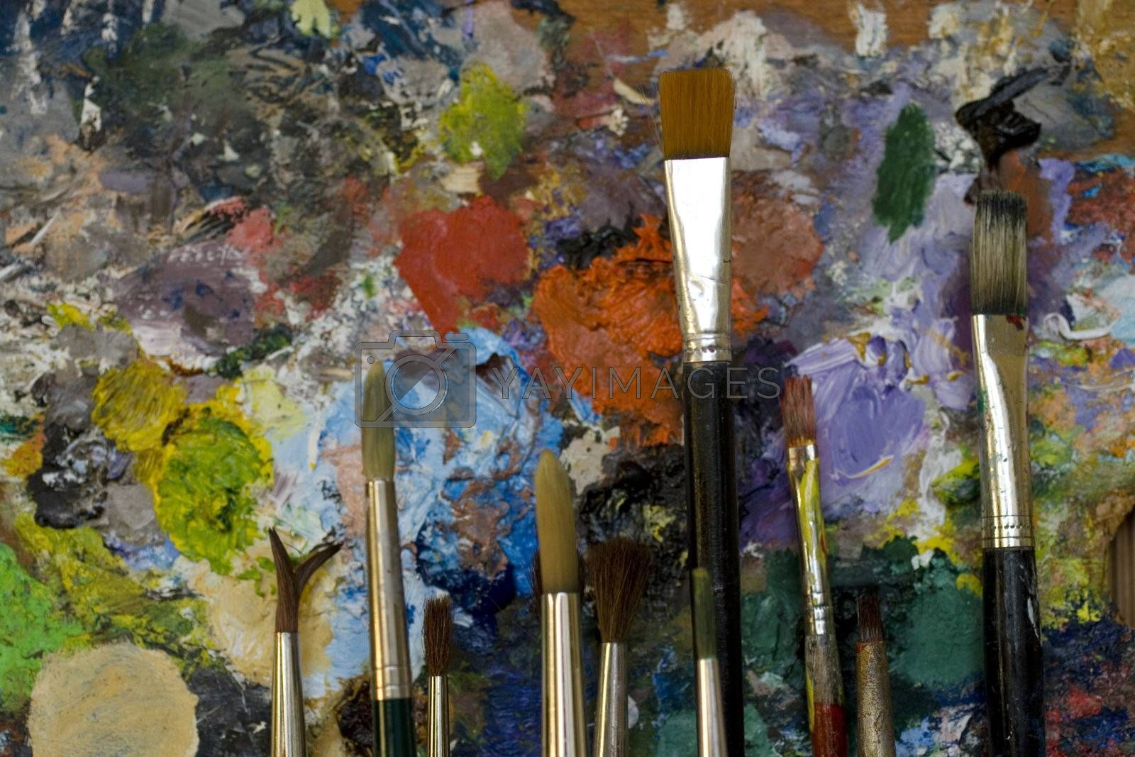 Paintbrushes used and dirty color. Palette on the background