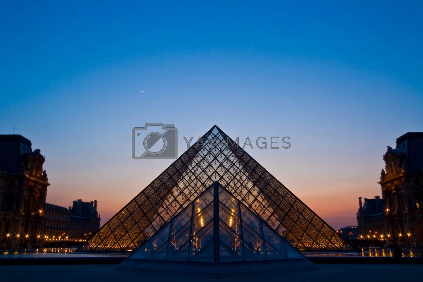 PARIS - APRIL 16: Double of Louvre pyramid shines at dusk during the Summer Exhibition April 16, 2010 in Paris. This is one of the most popular tourist destinations in France.