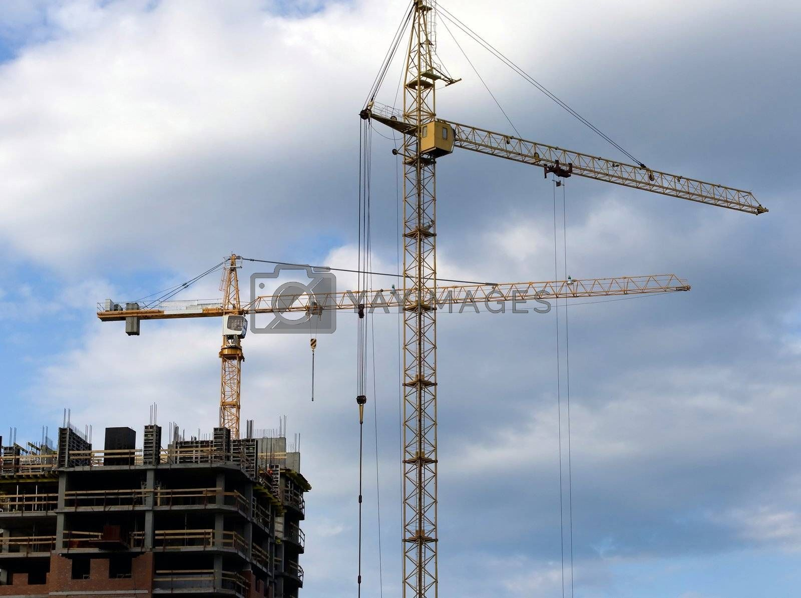 two cranes stand in front of a new building