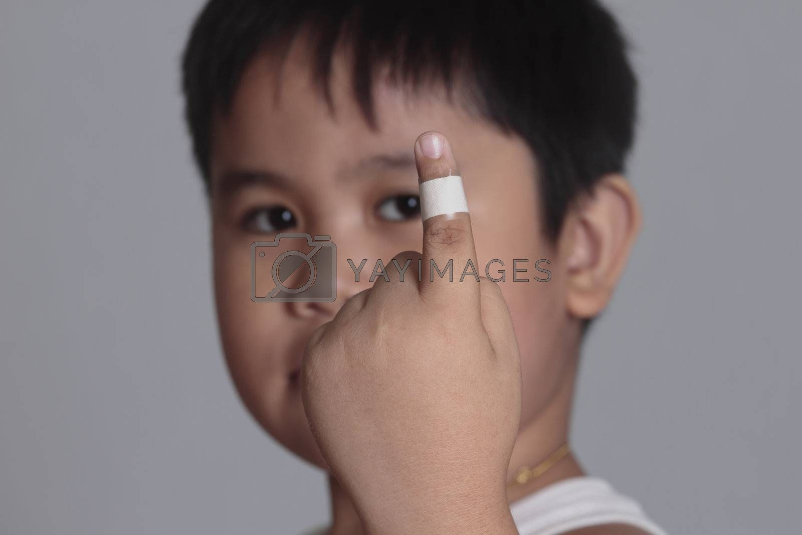 boy with a bandaged finger on gray background