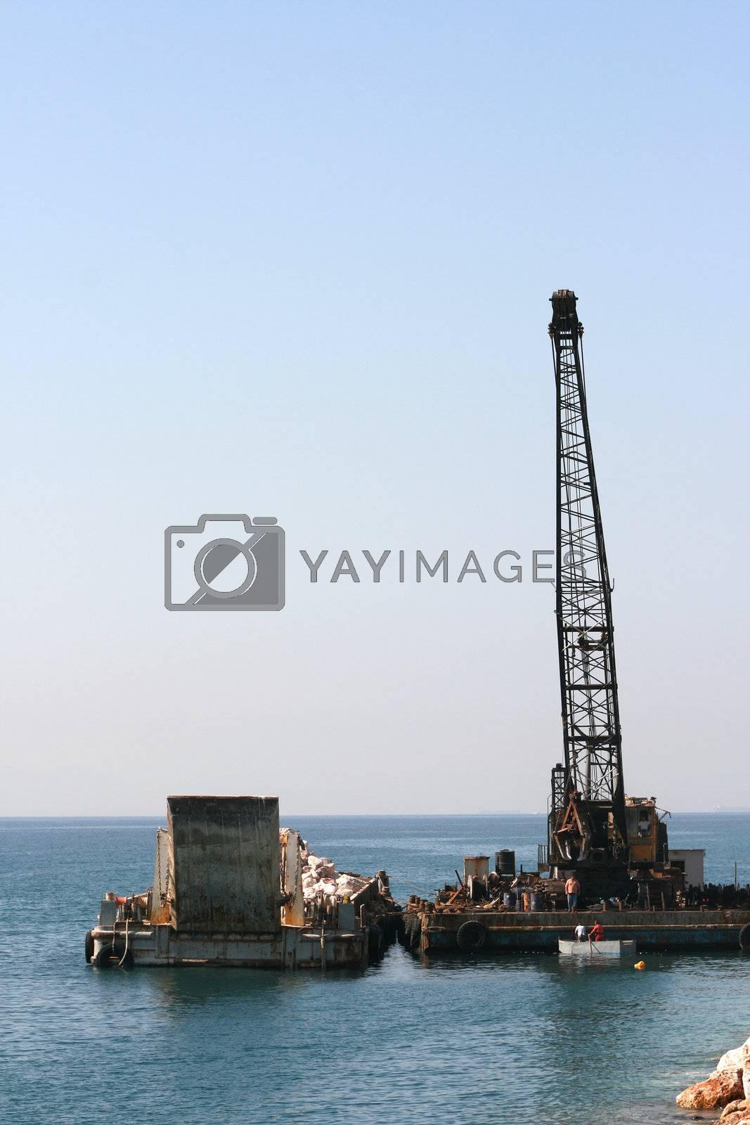 floating crane unloading flat barge full of stones