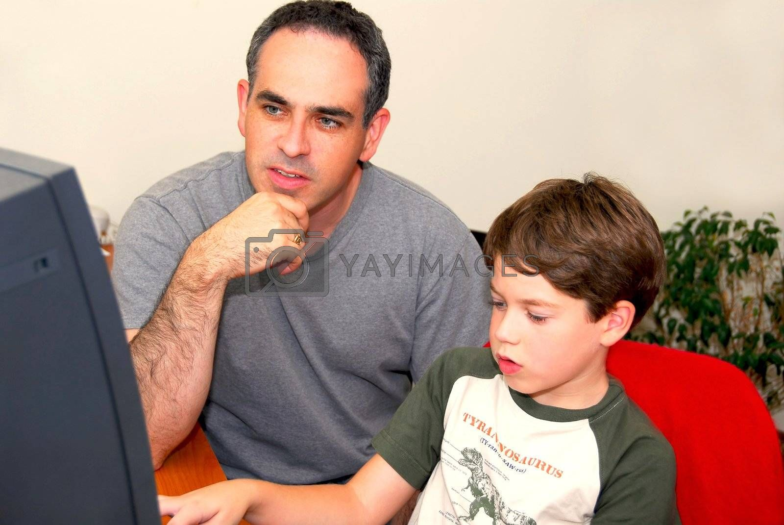 Father teaching his son to work on a computer