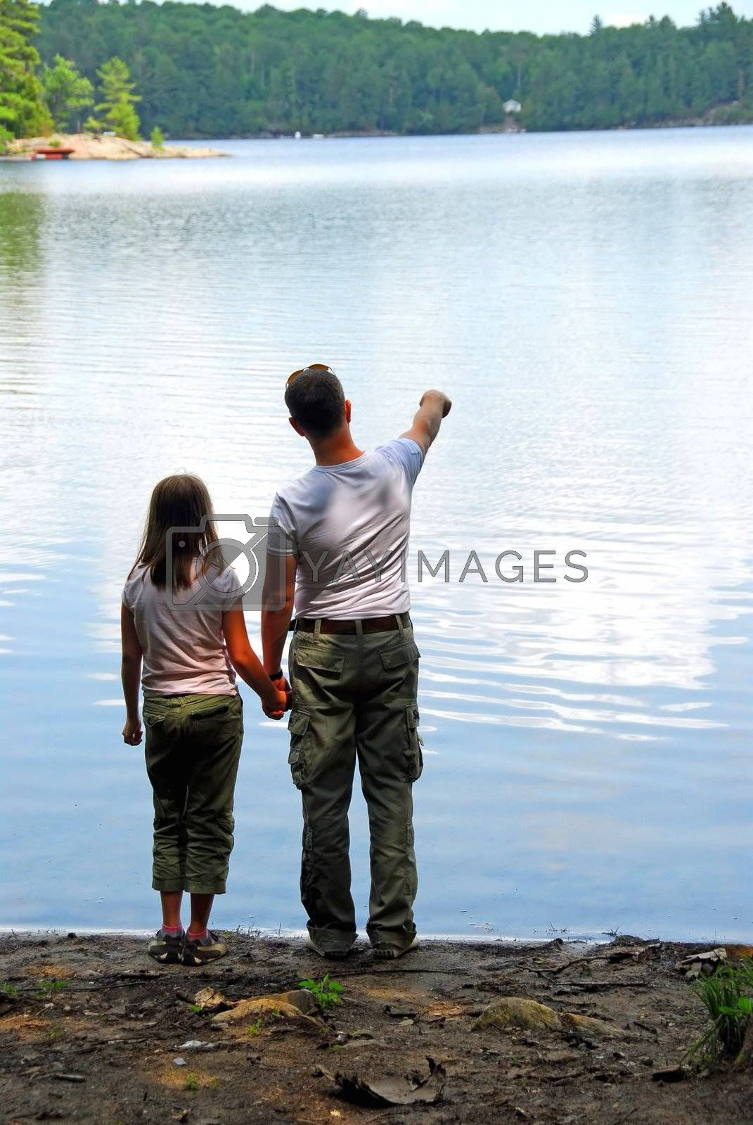 Father and daughter standing on the lake shore and looking at calm water, father pointing at somthing on the other shore