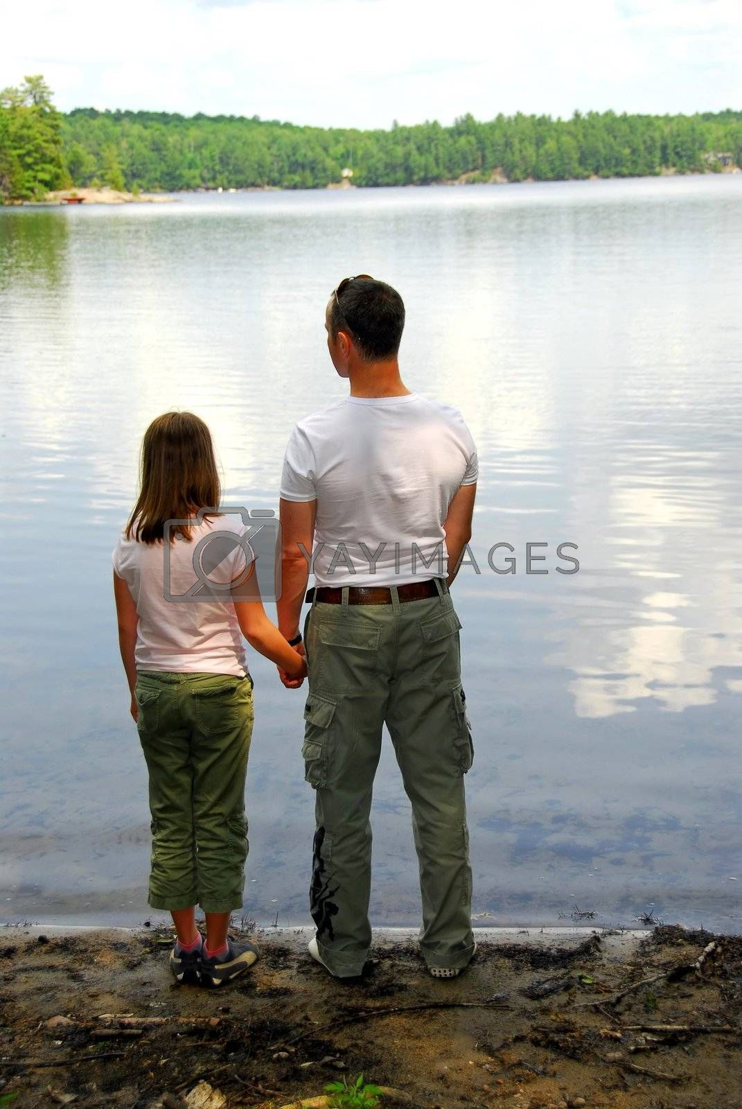 Father and daughter standing on the lake shore and looking at calm water