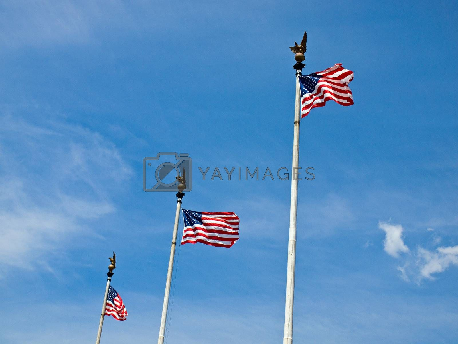 Three American Flags Waving Proudly on Tall Flagpoles
