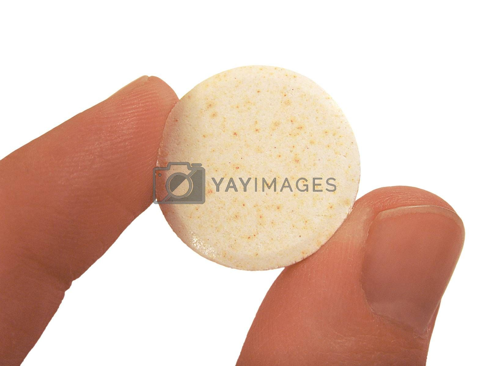 an effervescent tablet between finger and a thumb over white