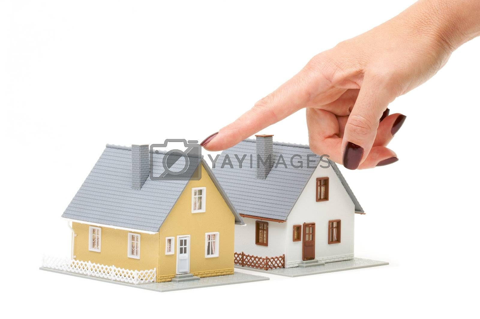 Female hand pointing at a house isolated on a white background.