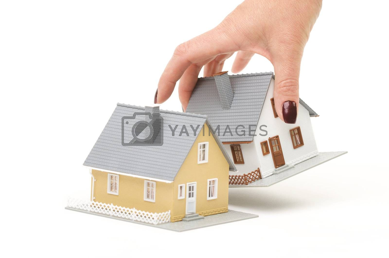 Female hand choosing a house isolated on a white background.