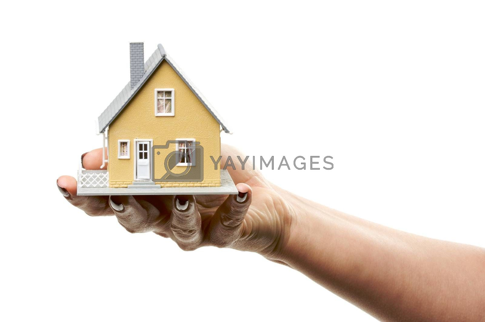 Female hand holding a house isolated on a white background.